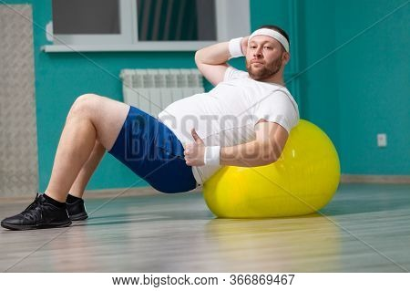Overweight Man Is Lying On A Fitness Ball During Group Fitness Classes. Fat Man Looks Satisfied With