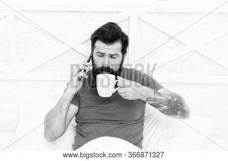 Just Want To Sip Coffee. Bearded Man Talk On Phone Drinking Coffee In Bed. Drinking Tea Habit. Drink