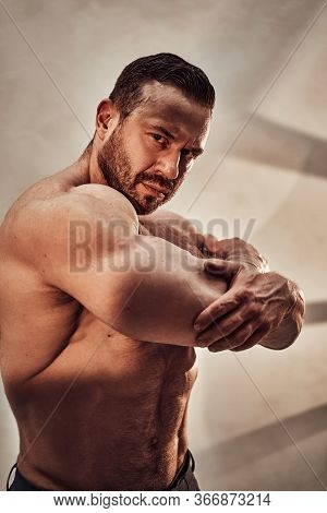 Sportive Adult Male Without Shirt Posing, Showing His Triceps Muscles And Looking At The Camera In A