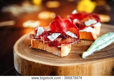 Top View On Bruschetta With Ham Topping (jamon, Prosciutto Crudo, Hamon) With Sauce On The Wooden Bo