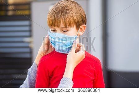 Mother Puts Her Son A Face Protective Mask Outdoors. Stop Coronavirus Spreading. Coronavirus Quarant
