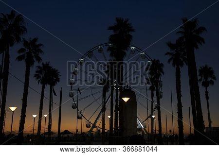 Adelaide, Australia - March 8th, 2020:the Ferris Wheel On The Beach Of Adelaide, Australia, At Sunse