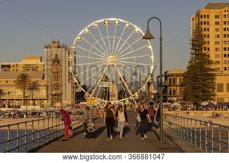 Adelaide, Australia - March 8th, 2020:tourists And A Fisherman On The Wharf Under The Ferris Wheel O