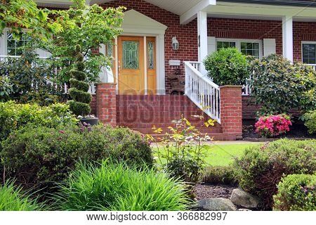 Beautifully and professionally landscaped entrance to a large brick house in an exclusive Canadian neighbourhood.