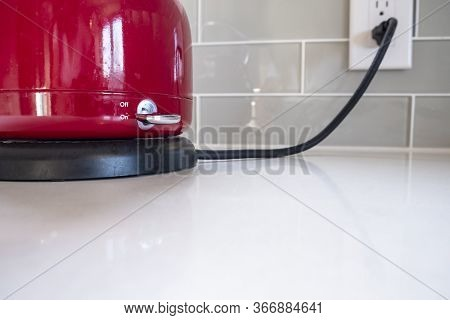 Red Electric Kettle Is Plugged In And Turned On To Boil Water On A White Quartz Counter Top In A Mod