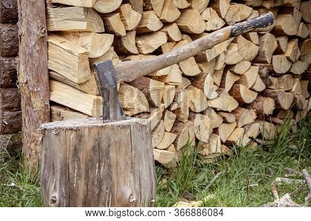A Woodcutter's Metal Axe With A Wooden Handle Is Stuck In A Log For Chopping Wood Against The Backgr