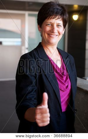 Portrait Of A Mature Businesswoman Holding Thumbsup