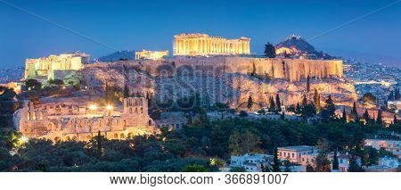 Panoramic view of the Acropolis Hil  with Parthenon, above of the city skyline during evening blue hour in Athens, Greece