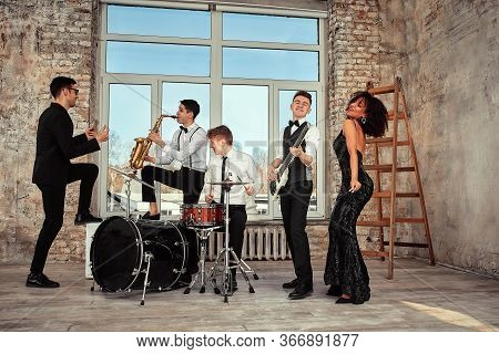 Repetition Of Multi Ethnic Jazz Band In Loft. Bass Guitar Player, Electric Guitar Player, Saxophonis