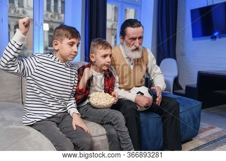 Likable Concentrated Senior Bearded Grandfather With His Cheerful 10-15s Grandsons Spending Their Fr