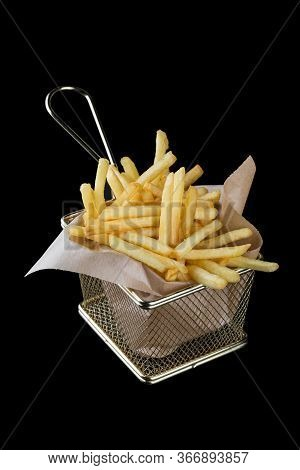 A Serving Of Golden French Fries Is Served In A Metal Mesh. Isolated On A Black Background.