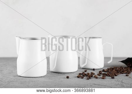 Three White Milk Jugs On A Gray Decorative Background. Coffee Beans Are Scattered Nearby.