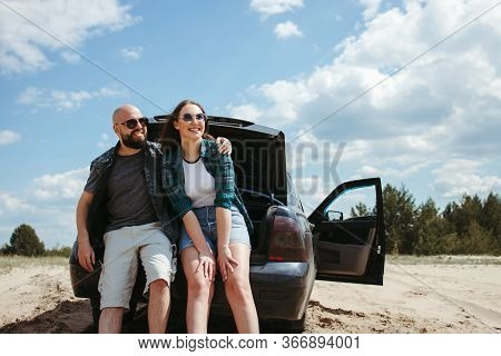 Young Joyful Couple Traveling By Car. Man And Woman Sitting In Car Trunk Resting. Tourism Lifestyle,