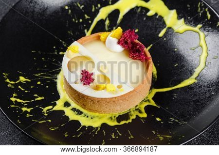 Lemon Tart On A Black Plate. Beautiful Serve From The Cook In A Restaurant.