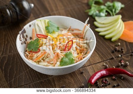 Vegetarian Salad Of Fresh Spring Vegetables. Cabbage, Carrots, Apple And Chili Peppers.
