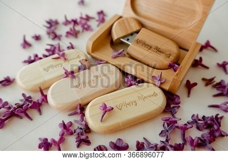Wooden Brown Usb Flash Drives With Boxes With The Text Happy Moments With Lilac Petals On A White Ba