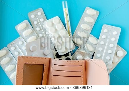 Empty Wallet With White Tablets Of Pills On  Blue Background