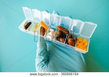 A Hand With A Medical Glove Holds Multi-colored Capsules, A Pill Box With Medicines On A Blue Backgr