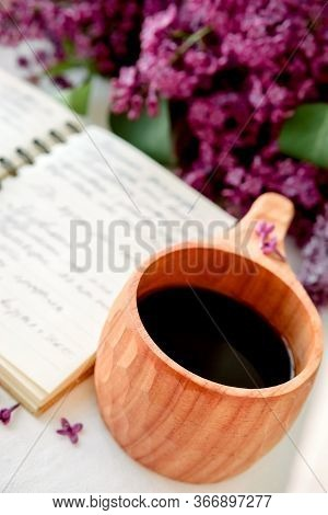 Wooden Finnish Cup With Coffee On The Table. Nearby Lies An Open Notebook For Notes And A Bouquet Of