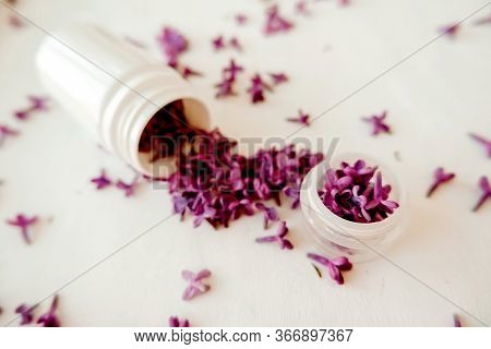 White Jar With Lilac Petals On A White Background, Facial Massager, Alternative Medicine And Skin Ca