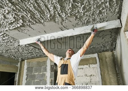 Plasterer smoothing plaster mortar on ceiling with screeder