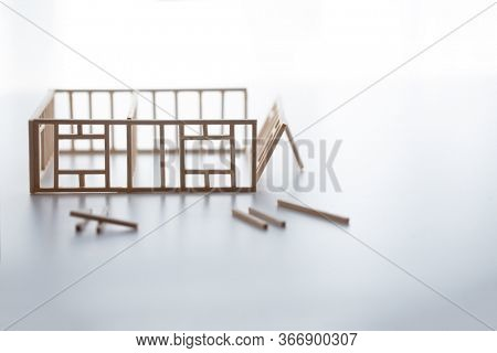 Building a house or a home. Frame work of a house with walls being erected. Natural white background.