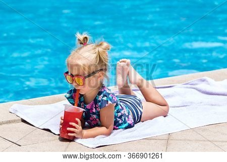 Beautiful Little Girl, Cute Toddler With Blonde Hair In Swimwear, Sitting At A Swimming Pool And Dri