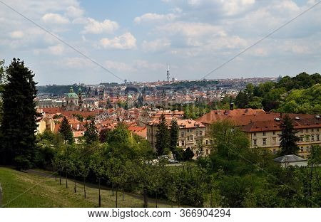 Views Of The Roofs Of Prague Houses In The Background Of The Vltava And The Sky With Clouds