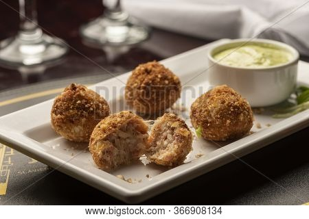 Arancini Balls Stuffed With Cheese On White Plate, Wine Glasses And Napkin