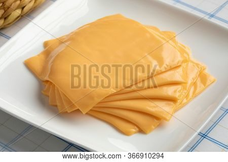 Slices of cheddar cheese ready to melt close up