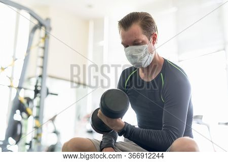 Young Man With Mask Sitting While Exercising With Dumbbell At Gym During Corona Virus Covid-19