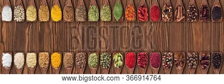 Spices And Herbs From Different Countries In Wooden Spoons. Colorful Seasonings On   Table Backgroun