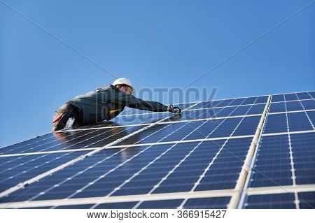 Male Worker Mounting Solar Modules, Panels And Support Structures Of Photovoltaic Solar Array. Elect