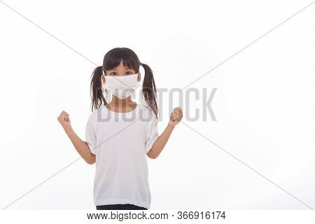 Asia Girl Wearing Mask To Protect Against Coronavirus, Girl Show A Fist Encourage To Fight Contagiou