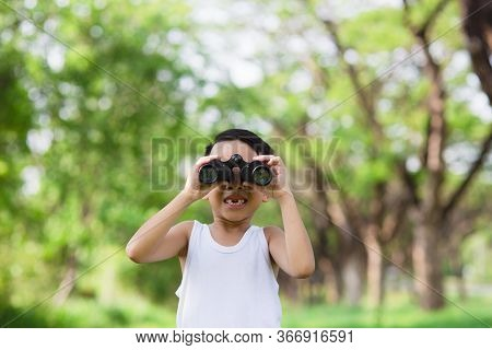 Little Boy Standing In A Green Grassy Field Scanning The Surrounding Woods With Binoculars As He Exp
