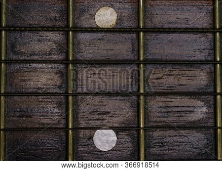 Close-up Picture Of A Guitar With A Fingerboard Made Of Wood With A White Inlay And A Very Old Guita