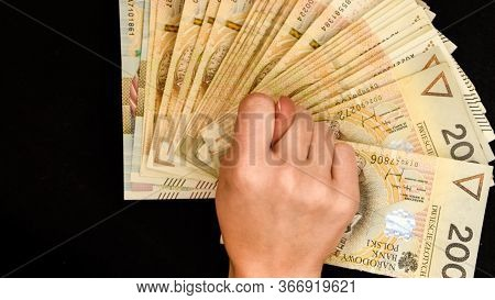 Polish Zloty Currency, Hand Holding Polish Zloty Cash On The Black Background