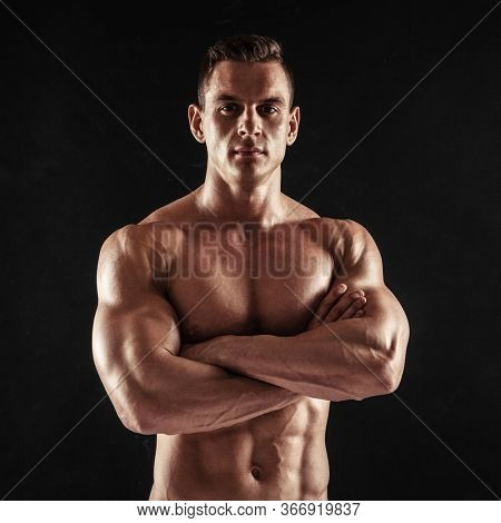 Fitness in gym, sport and healthy lifestyle concept. Handsome athletic man showing his trained body on dark background. Bodybuilder male model standing with crossed arms and tight muscles.