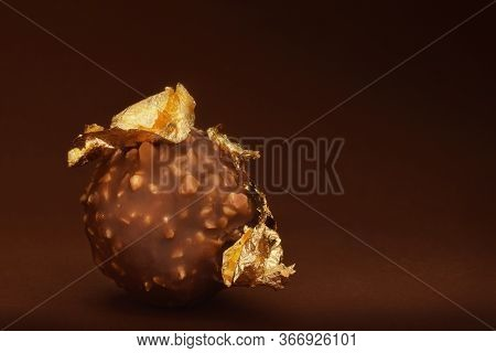 Chocolate Praline With Edible Gold Leaf. Low Key Food Background