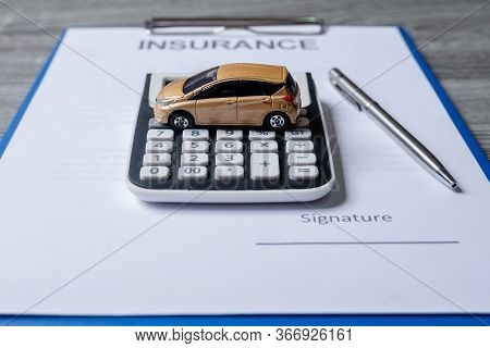 Car With Calculator And Pen On Insurance Documents. Car Insurance Concept.