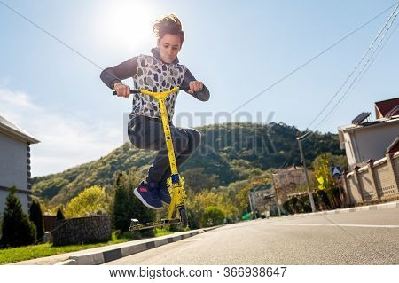 A Teenage Boy Performs A Trick On A Scooter, Bouncing Up On It. In The Background, An Empty Street A