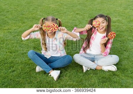 Holiday Food. Sweet Childhood. Happy Children Hold Candy Sit Green Grass. Candy Shop. Lollipop Treat