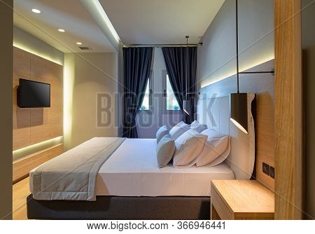 Side View Of Modern Bedroom Interior With Wooden Panel, Flat Tv, Backlight, Textile Headboard. Styli