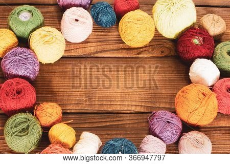 Group Of Multi-colored Woolen Clews With Crochet For Embroidery On A Wooden Background With Copy Spa