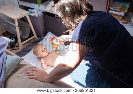 Babysitter Soothing Baby Lying In Beddings, Playing With Child With Rattle Toy. Staying At Home And