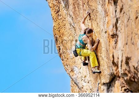 Athletic Beautiful Woman Climbs An Overhanging Rock With Rope, Lead Climbing. Sport Climbing Outdoor