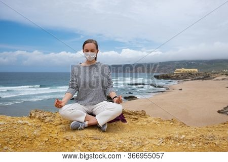 Peaceful Woman Wearing Face Mask, Meditating In Lotus Pose, Keeping Arms In Zen Gesture. Front View.