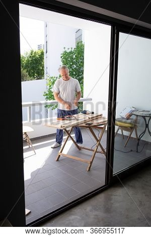 Senior Grey-haired Man In Home Clothes Looking At Wooden Parts Laying On Round Table. Craftsman Work