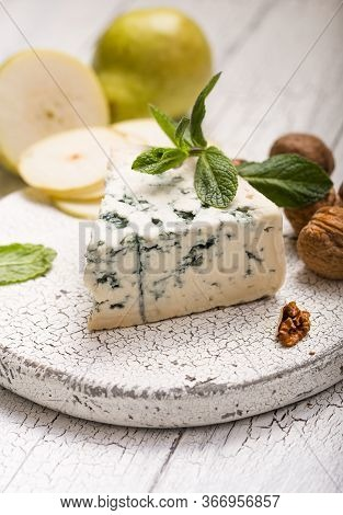 Segment Of Blue Mould Cheese - Gorgonzola With Pear And Walnuts On Wooden Board.  Top View Gorgonzol