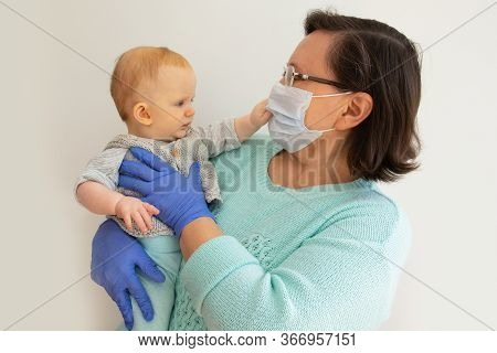 Grandma In Mask And Gloves Holding Baby Granddaughter. Mature Woman With Little Child Posing Isolate